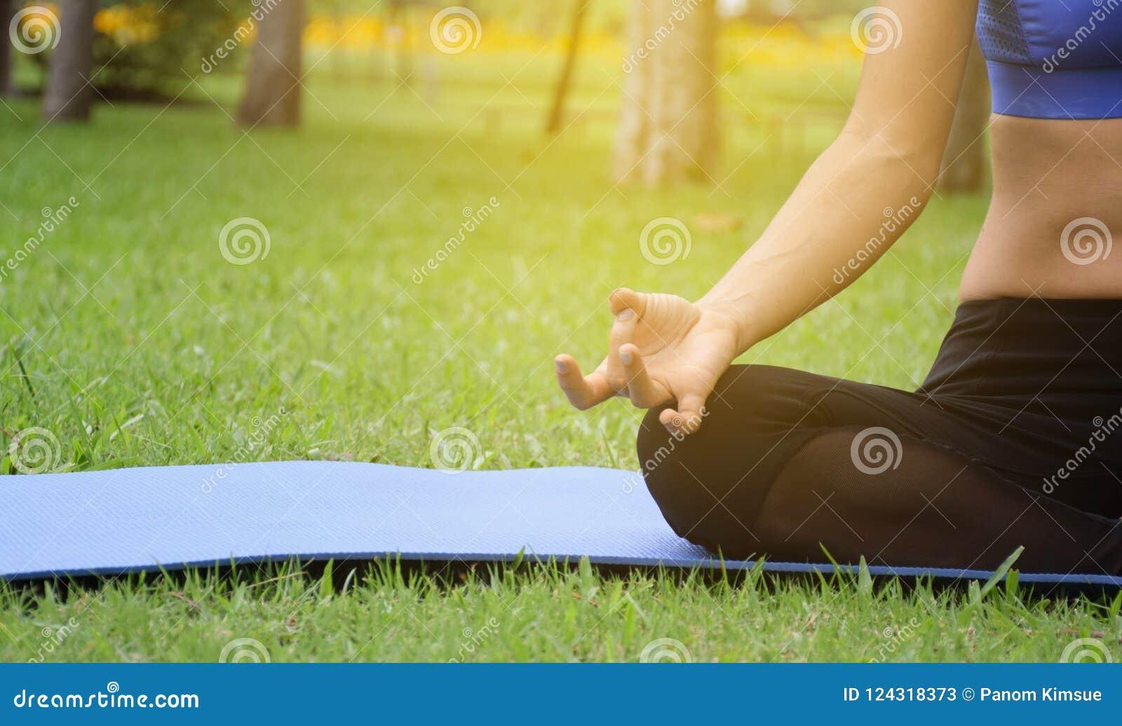 Le yoga de pratique de jeune femme en parc, étirage et flexibilité, a pratiqué pour la santé et la relaxation