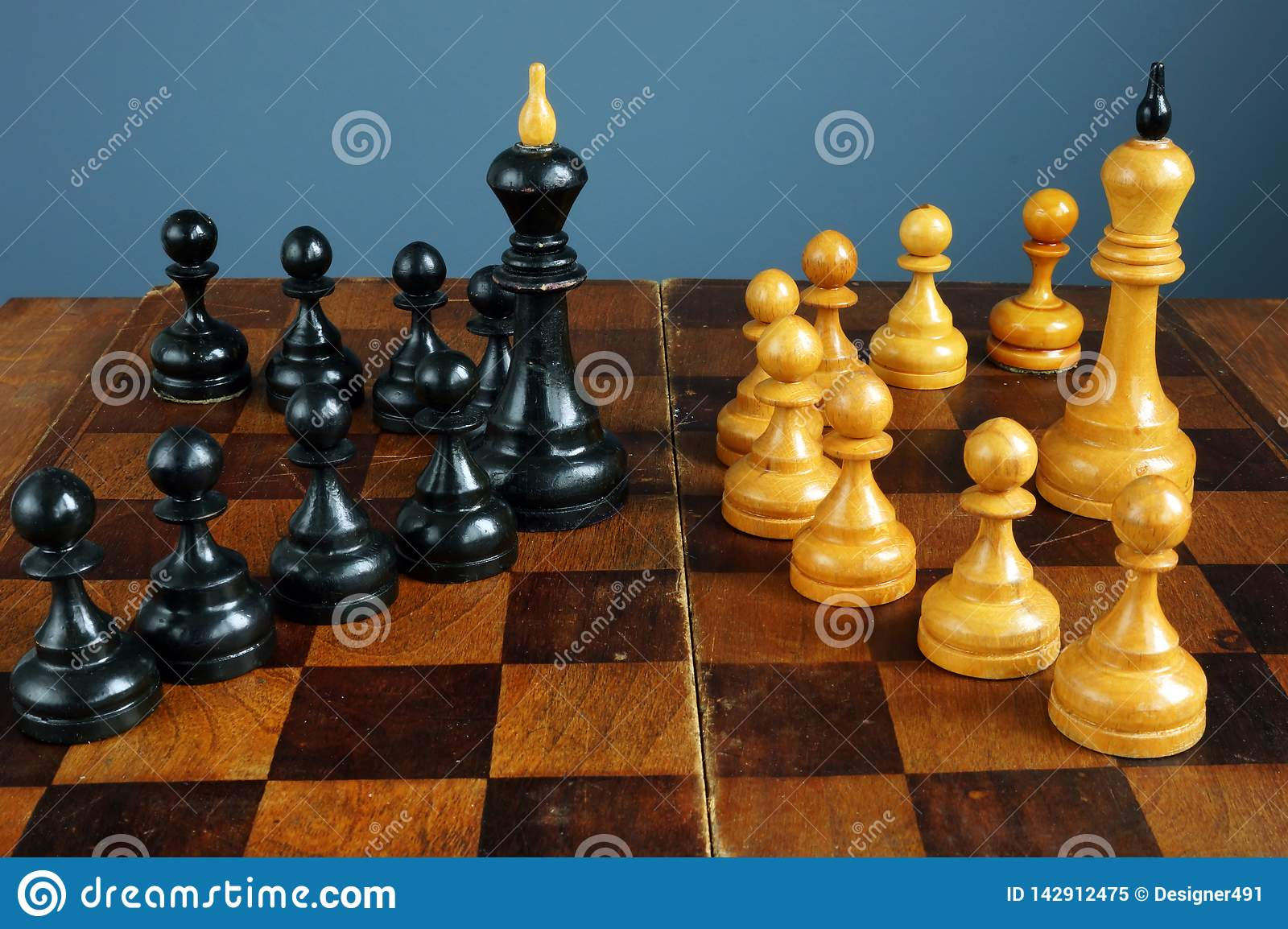 Leader vs boss or manager. Chess kings and pawns on desk