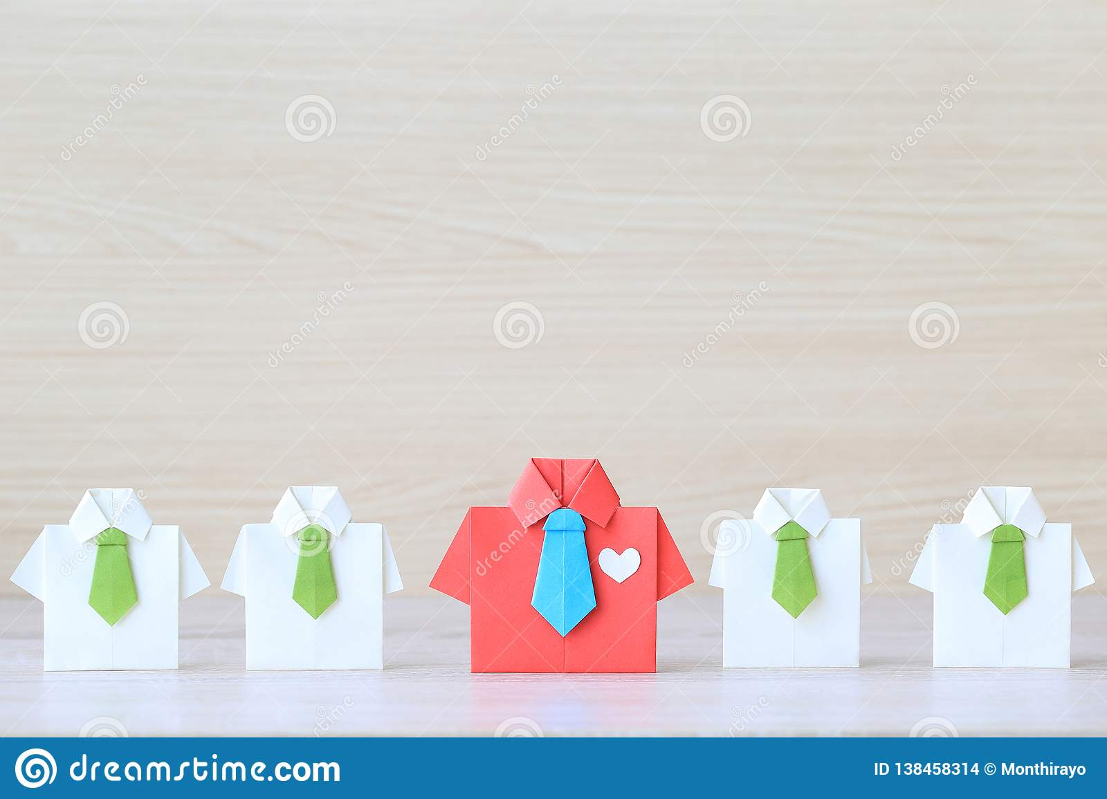Leadership and teamwork concept, Origami red shirt with tie and leading among small yellow shirt on wooder background