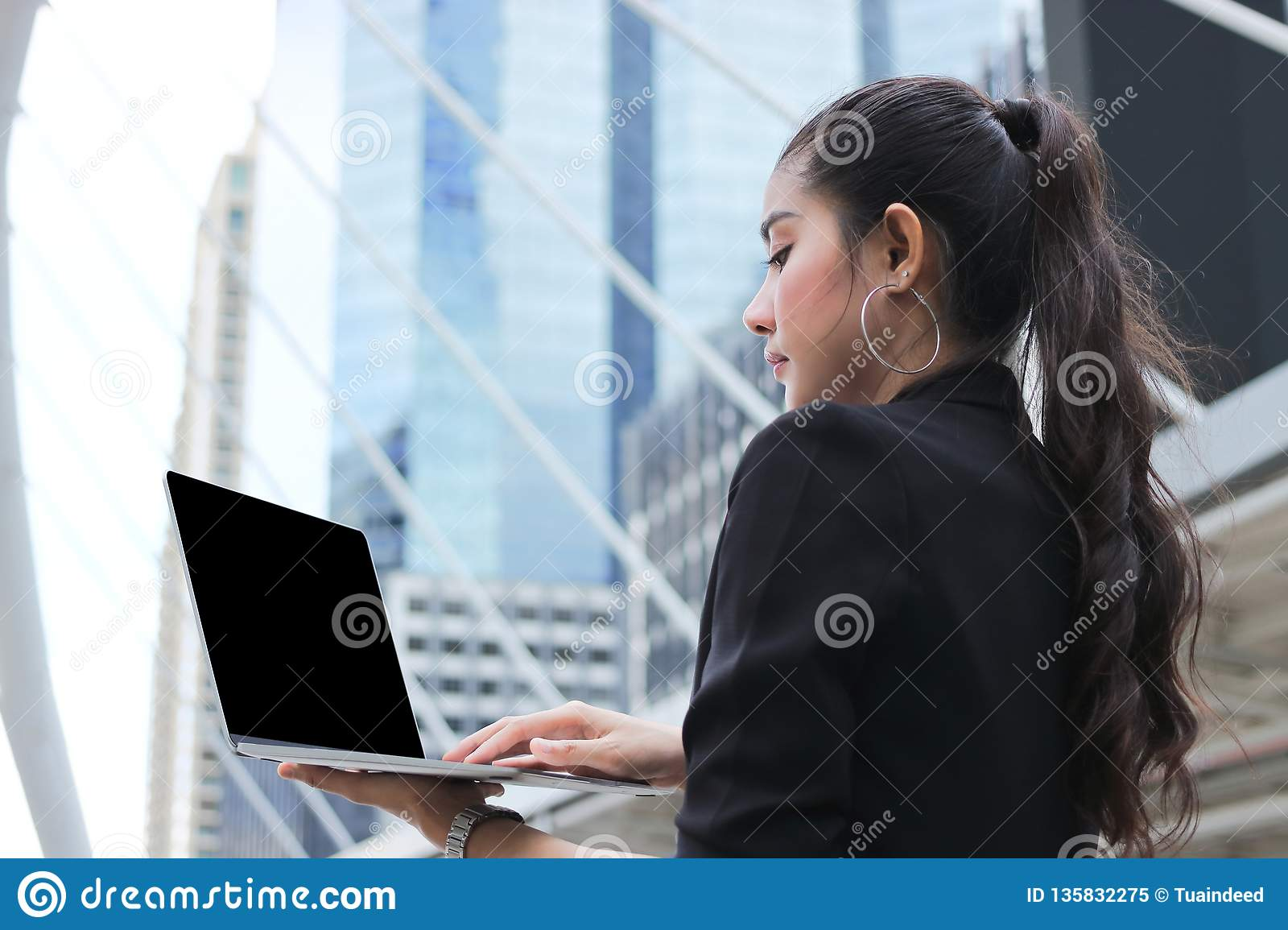 Leadership young Asian business woman working with laptop modern skyscrapers background