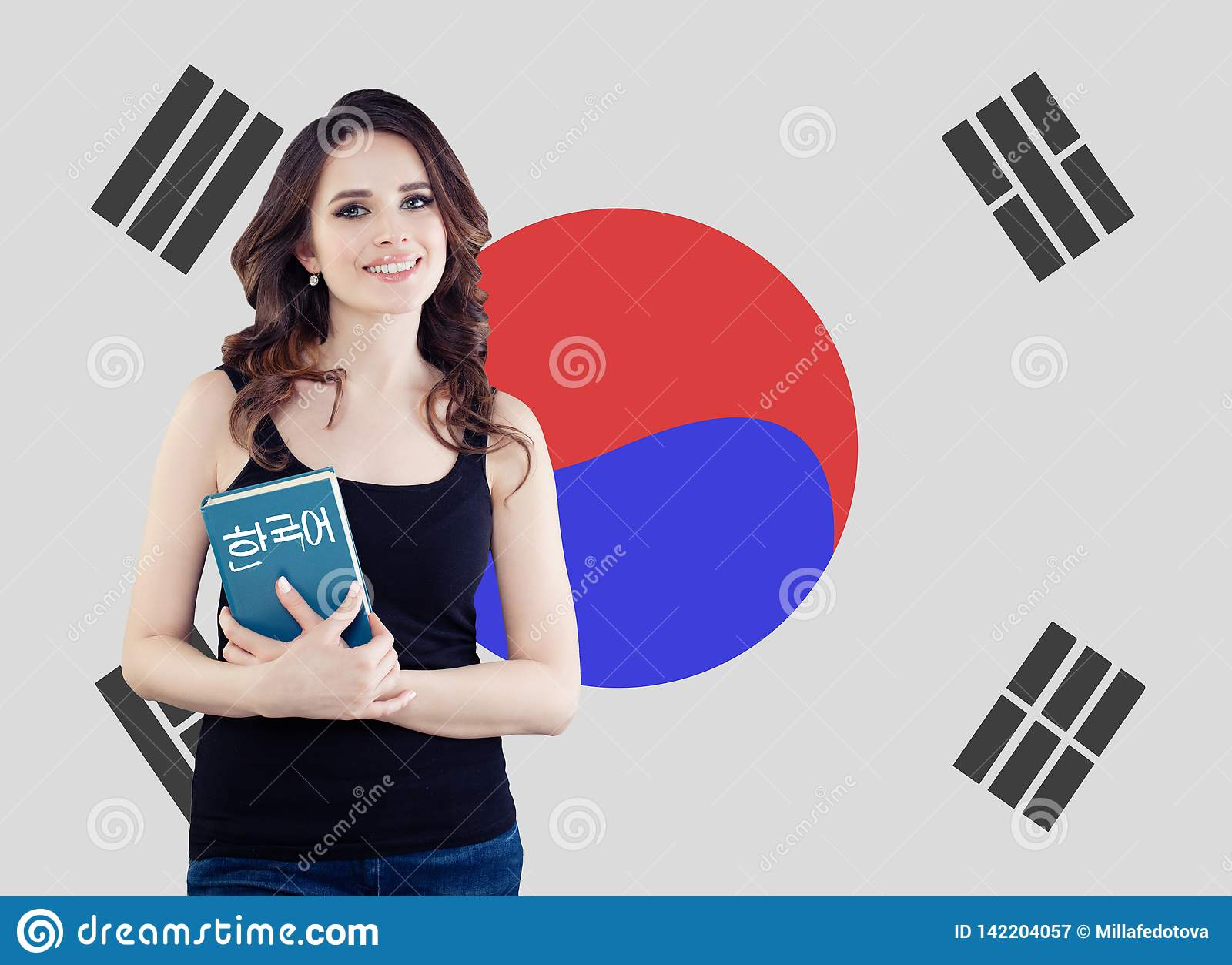 Learn korean language. Pretty young woman student with book against the South Korea flag background