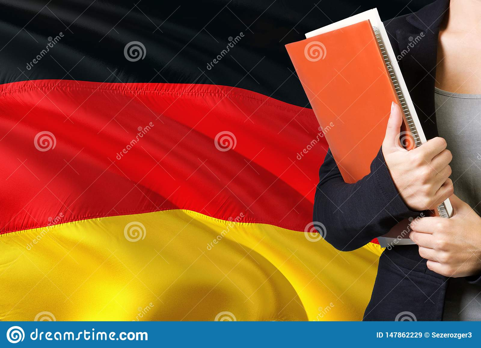 Learning German language concept. Young woman standing with the Germany flag in the background. Teacher holding books, orange