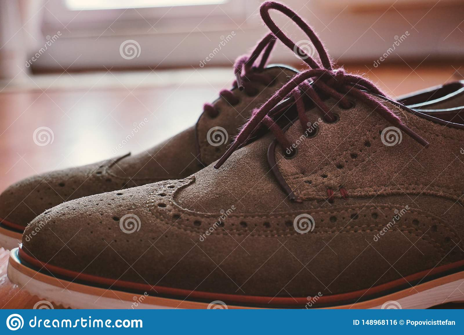 Leather Men`s Brogue Shoes with Colored Laces  on The Floor with Back Light  Closeup