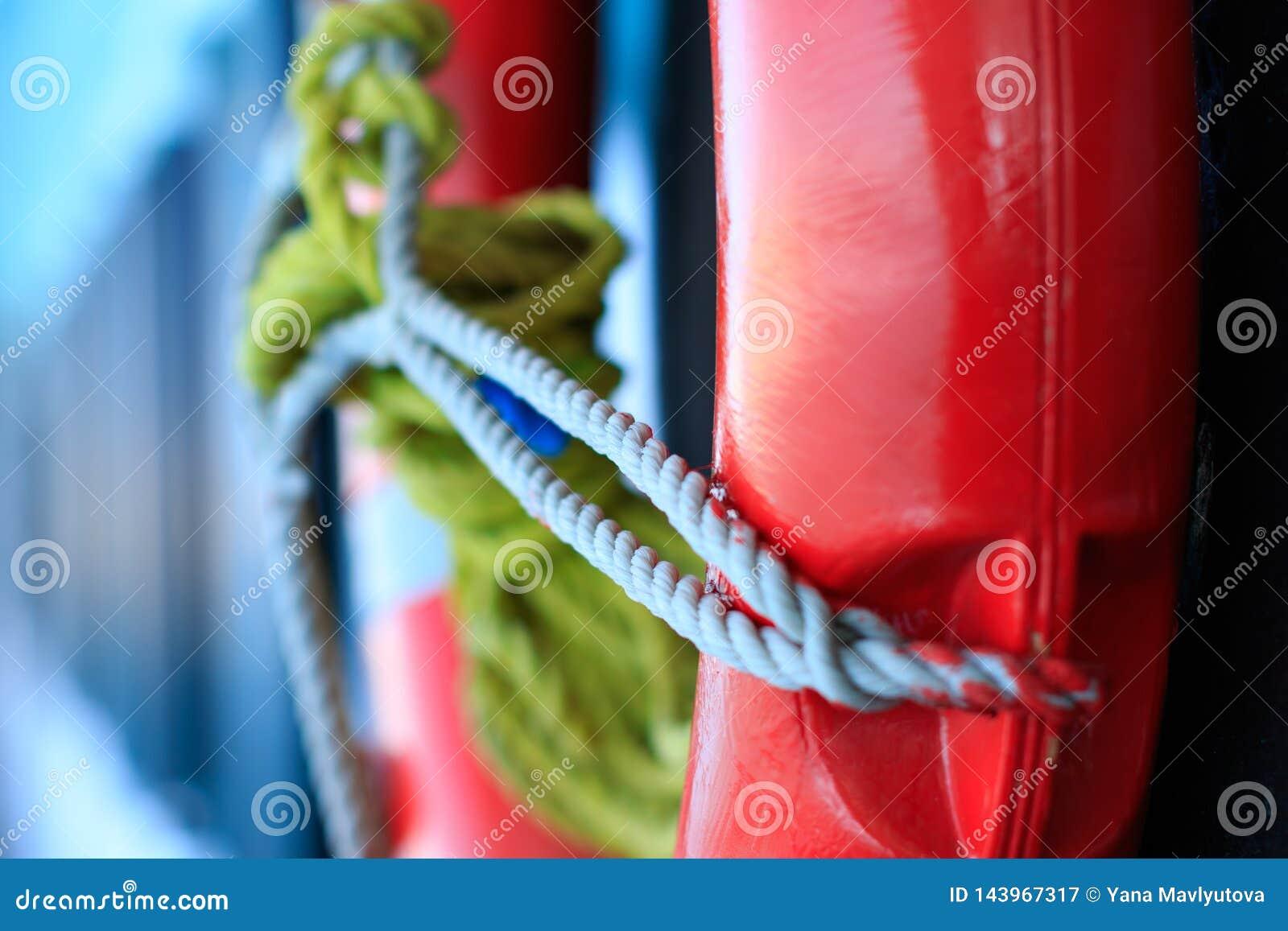 Lebenboje in der roten Farbe mit grauem Seilkabel auf Seeschiffsboot auf unscharfem blauem Hintergrund, Rettungsringsicherheitsre