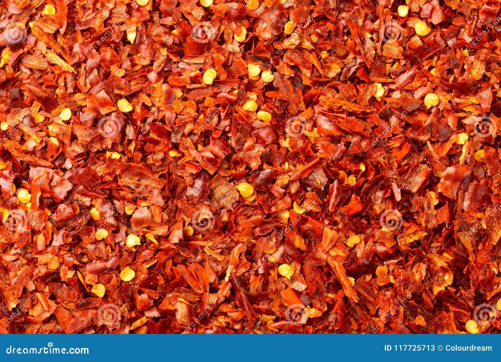 Lebensmittelhintergrund von getrockneten Flocken des roten Pfeffers, Draufsicht