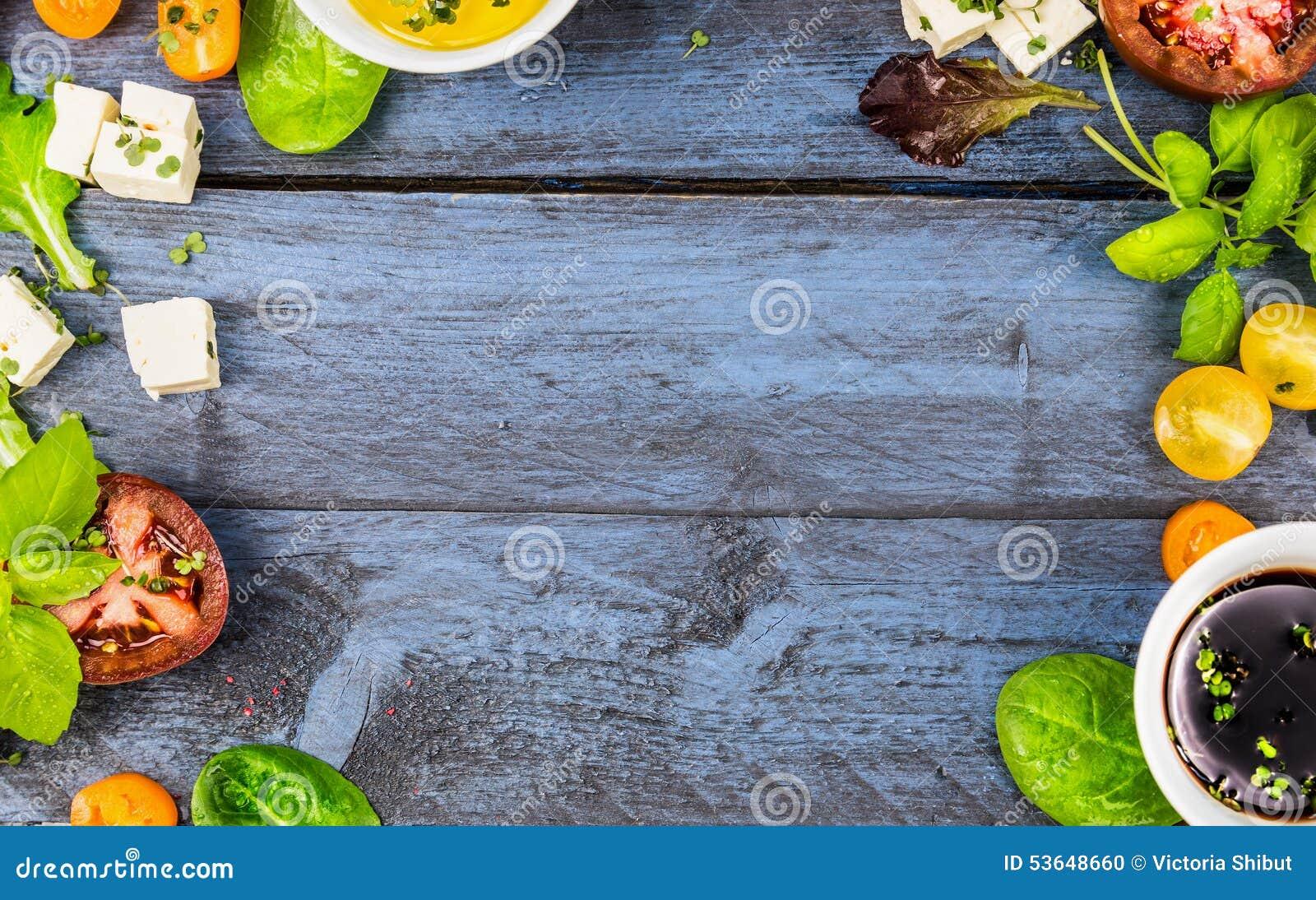 Lebensmittelrahmen mit Salatbestandteilen: Öl, Essig, Tomaten, Basilikum und Käse auf blauem rustikalem hölzernem Hintergrund