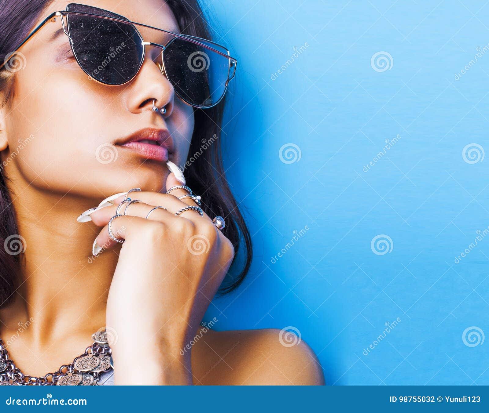 Lebensstilleutekonzept junges hübsches lächelndes indisches Mädchen mit den langen Nägeln, die Los Schmuck tragen, schellt, asiat