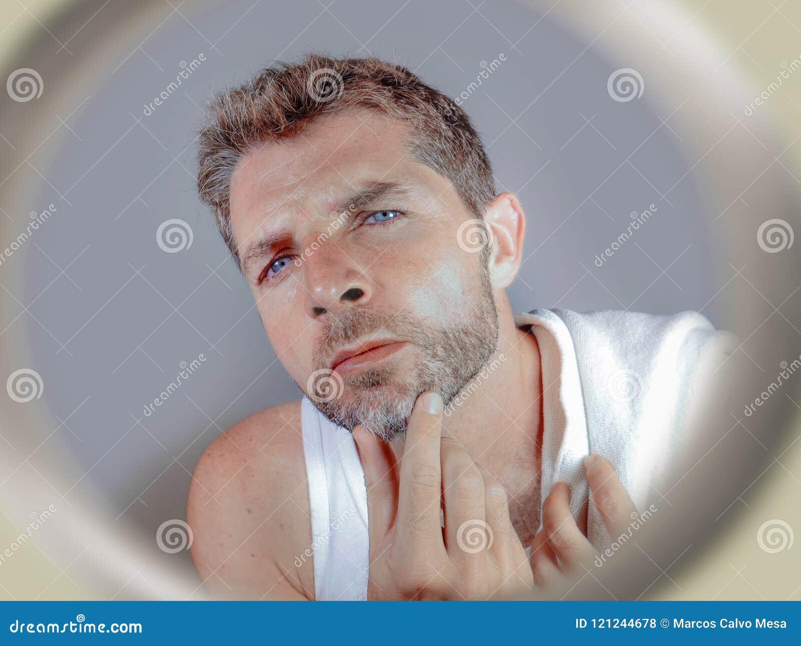 Lebensstilporträt des attraktiven besorgten und beteiligten kaukasischen Mannes, der den Badezimmerspiegel findet graueres Haar i