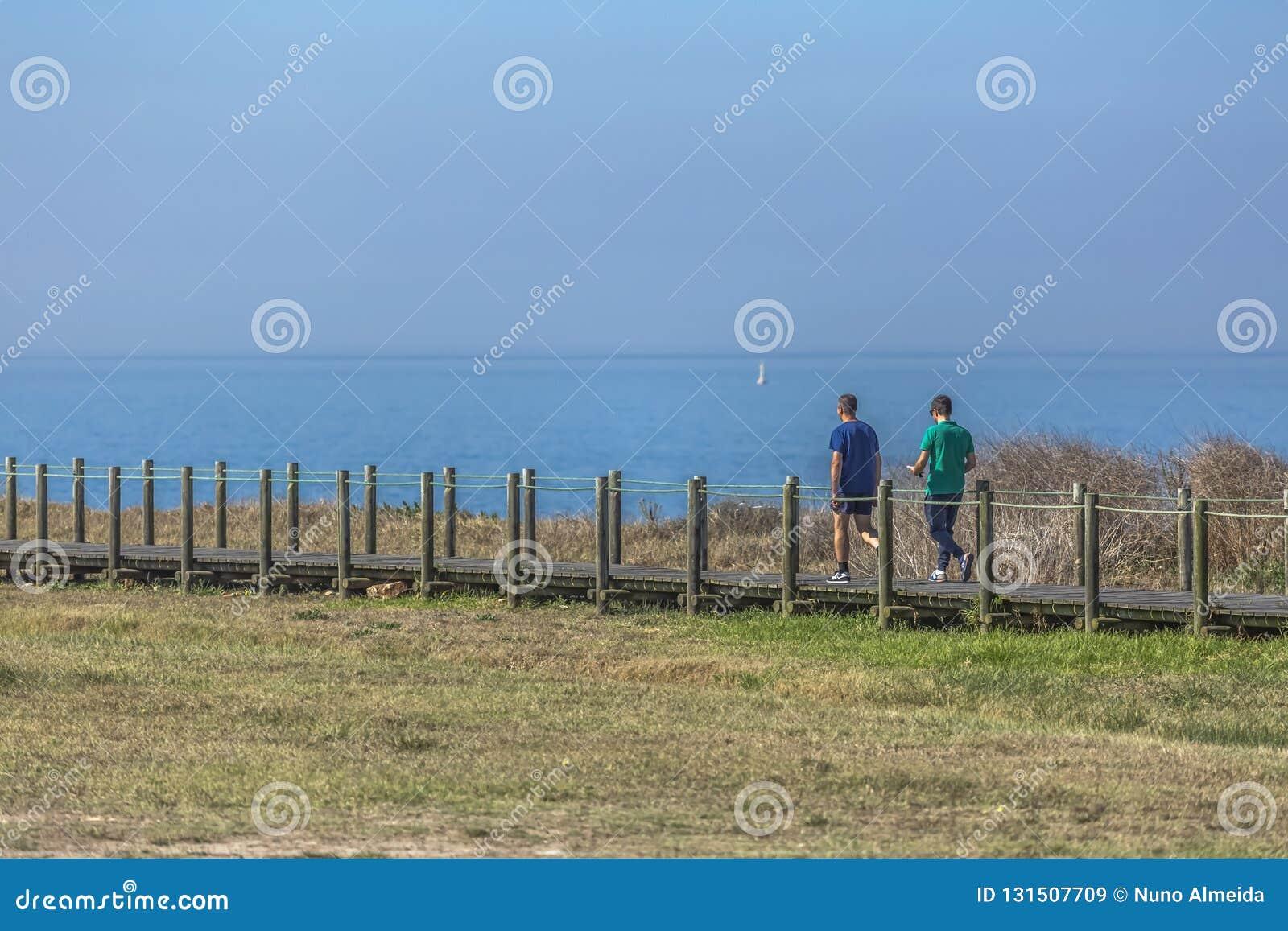 Leca da Palmeira/Porto/Portugal - 10 04 2018: Back view of two men, walking and talking on the eco pedestrian path, near the sea,