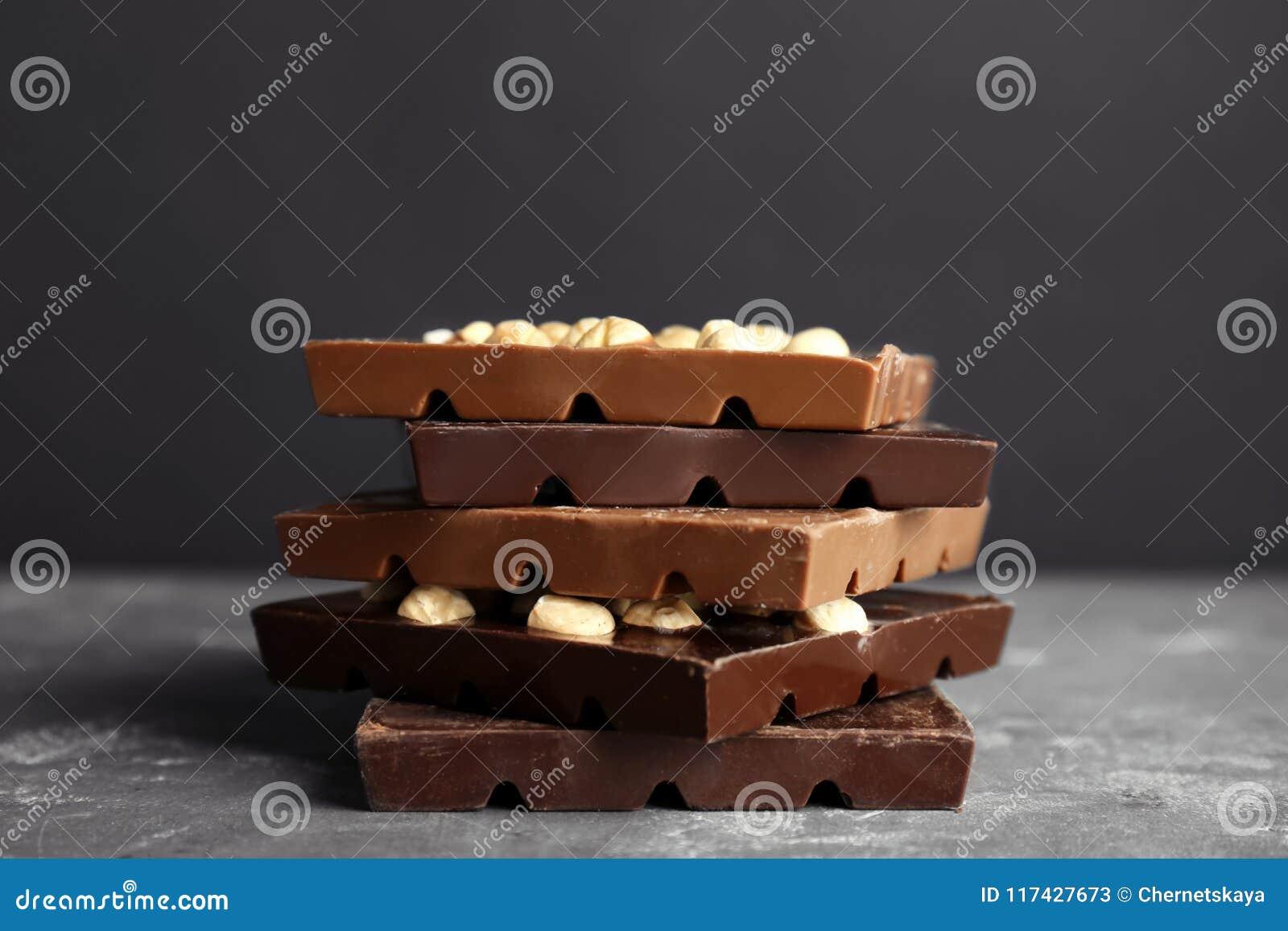 Leche deliciosa y barras de chocolate oscuras con la nuez en la tabla