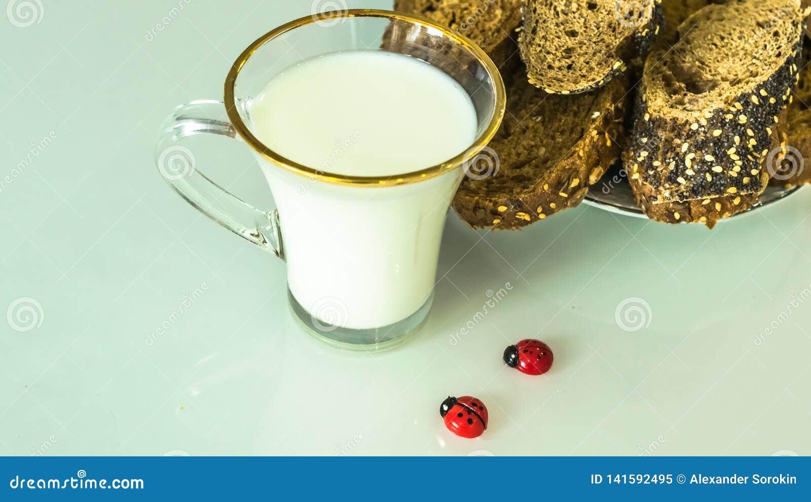 Leche en una taza en la tabla con el pan, secándose