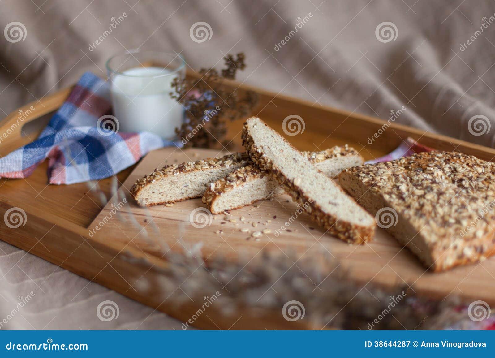 Leche y pan en la bandeja de madera