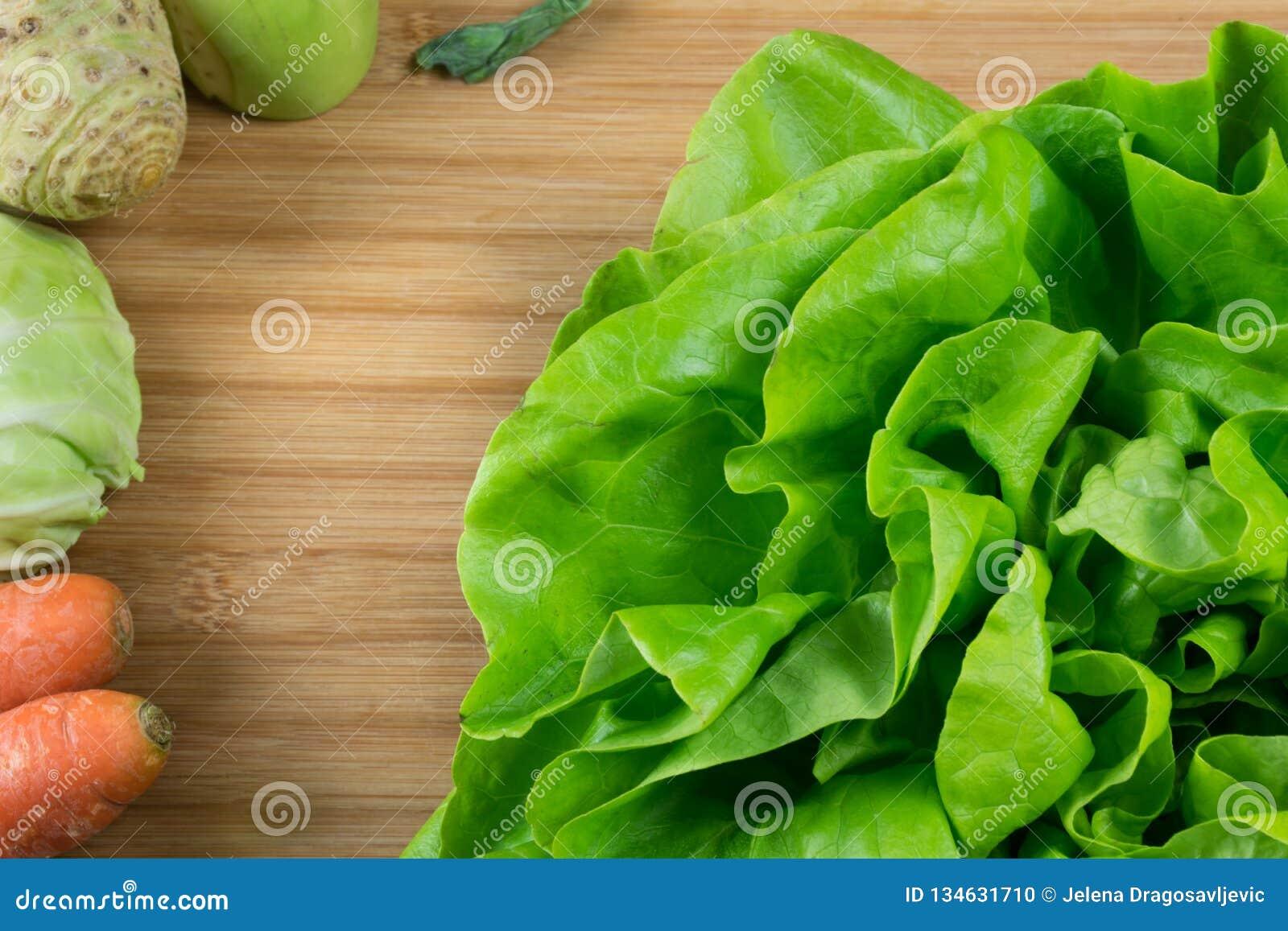 Lechuga verde fresca en el tablero del bacalao y verduras frescas, zanahoria, col, apio y colinabo en el lado