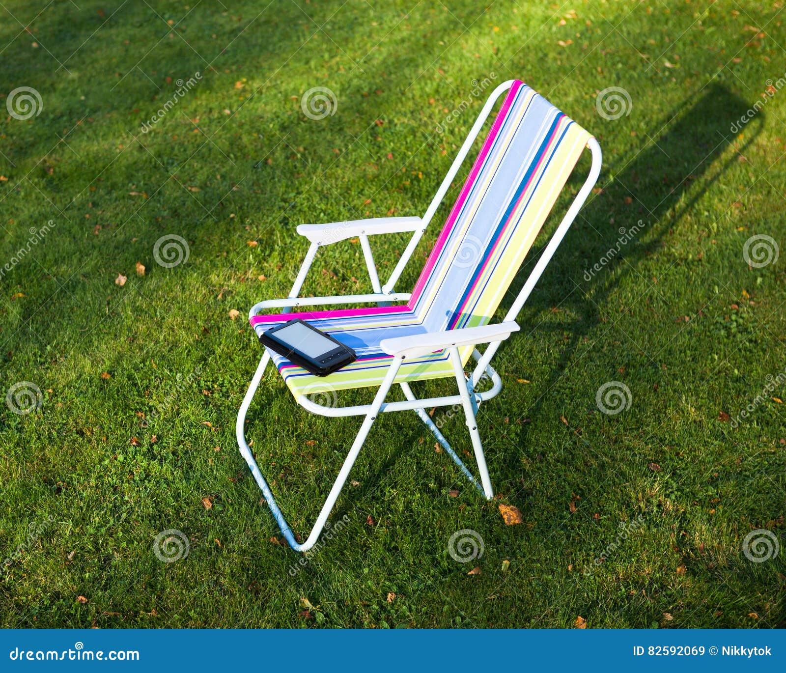 Lector en la silla, fondo de EBook de la hierba