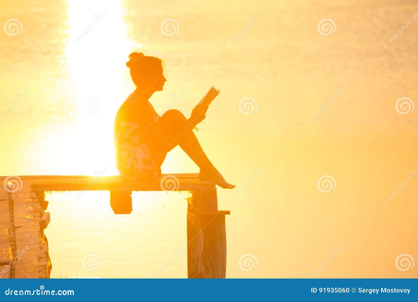 Lectura de la muchacha en el tiempo de la puesta del sol