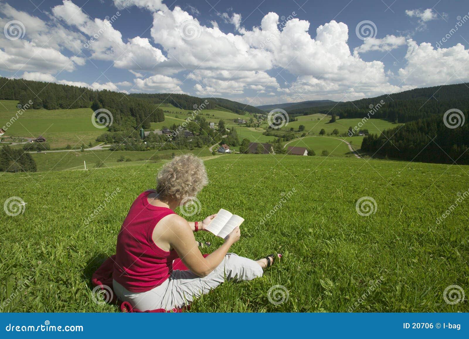 Lectura de la mujer en el prado