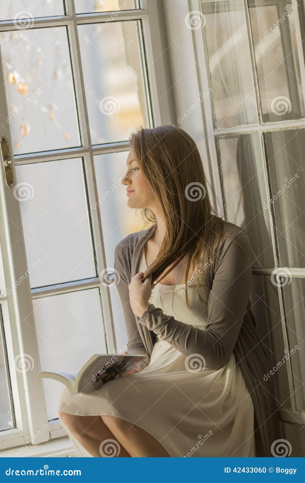 Lectura de la mujer joven por la ventana