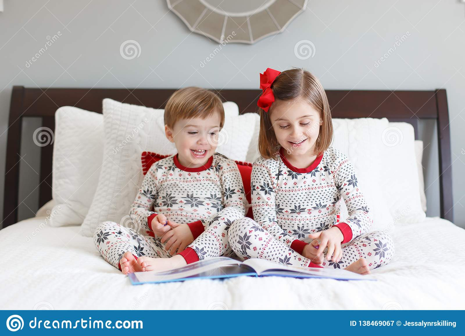 Lectura del muchacho y de la muchacha en cama con los pijamas de la Navidad