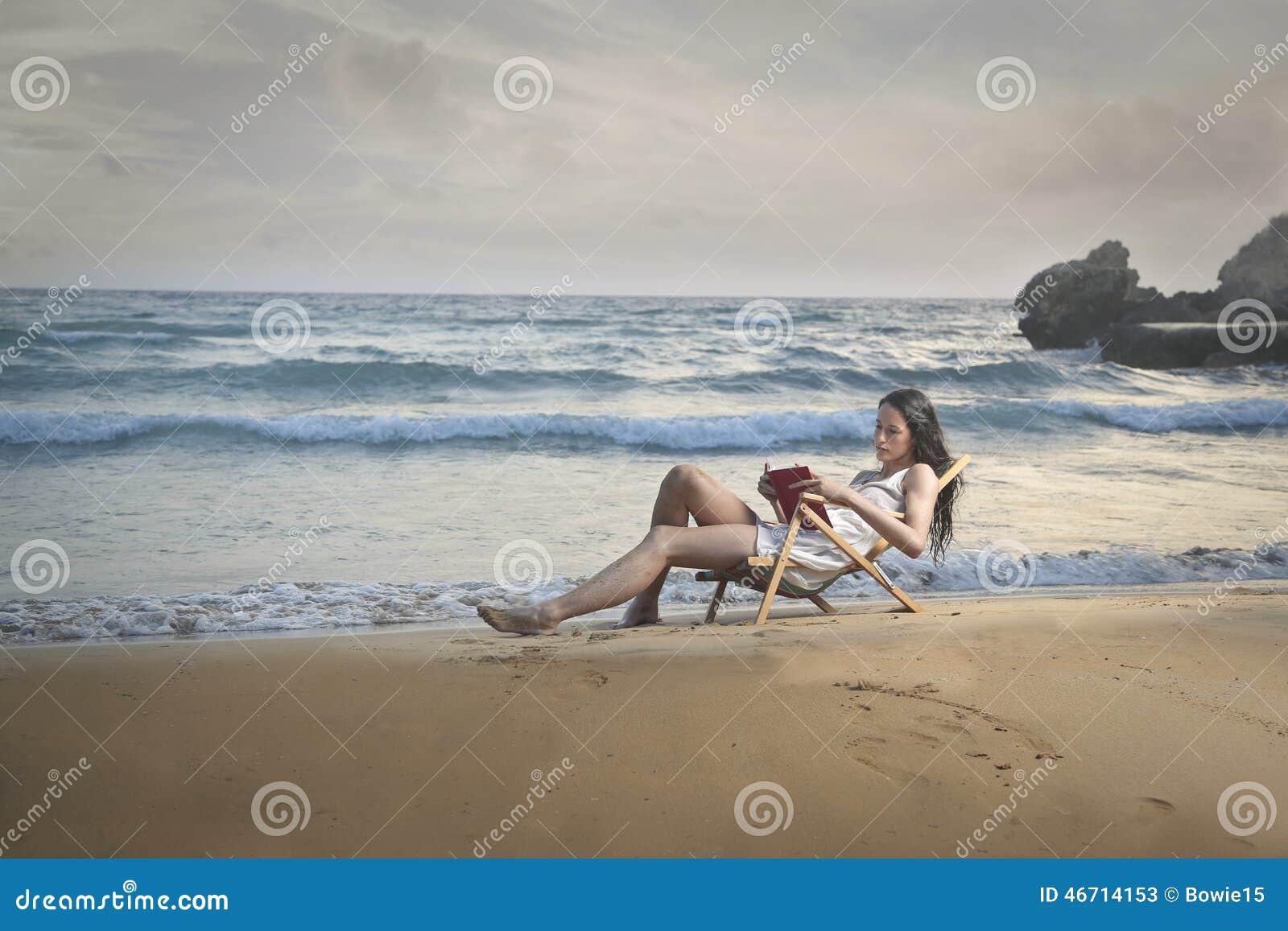 lecture d 39 un livre au bord de la mer image stock image. Black Bedroom Furniture Sets. Home Design Ideas