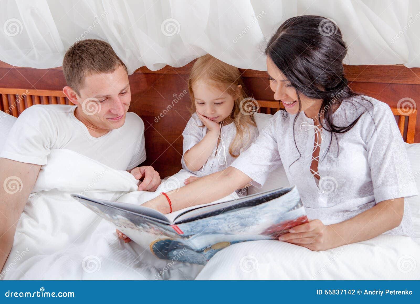 lecture de petite fille avec ses parents dans le lit photo stock image du conf rence famille. Black Bedroom Furniture Sets. Home Design Ideas