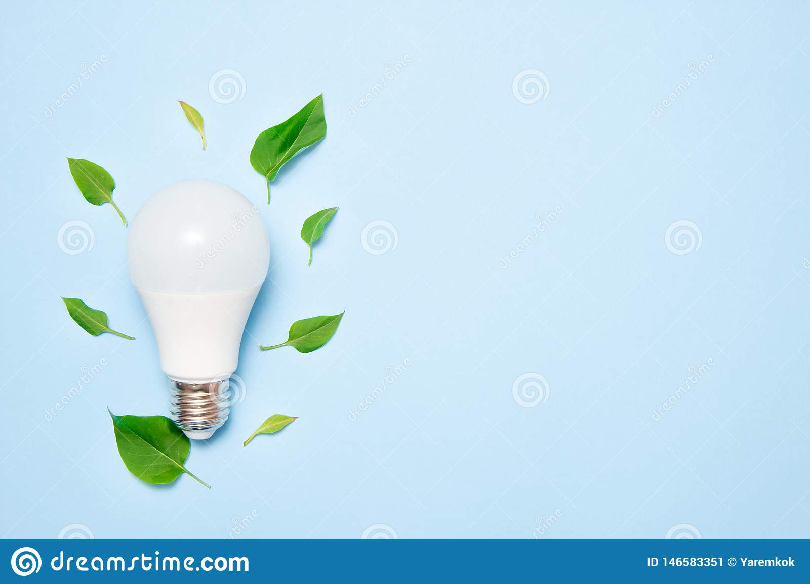 Led lamp with leaves on a blue background. Green energy efficiency concept. Top view