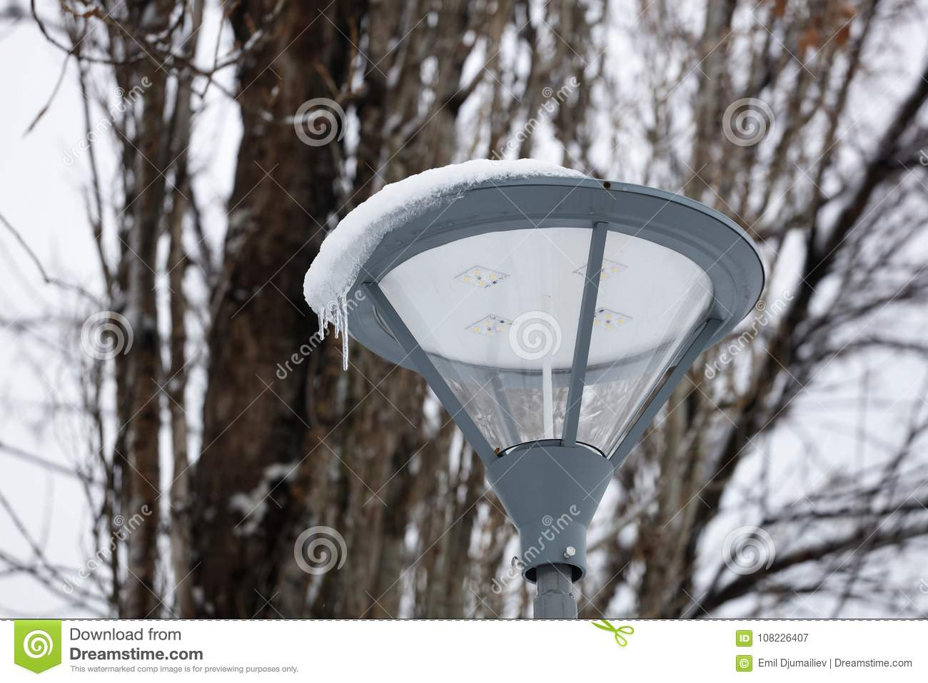 70bbc7711fde4 LED street light with grey pole and armature aigainst white winter sky.