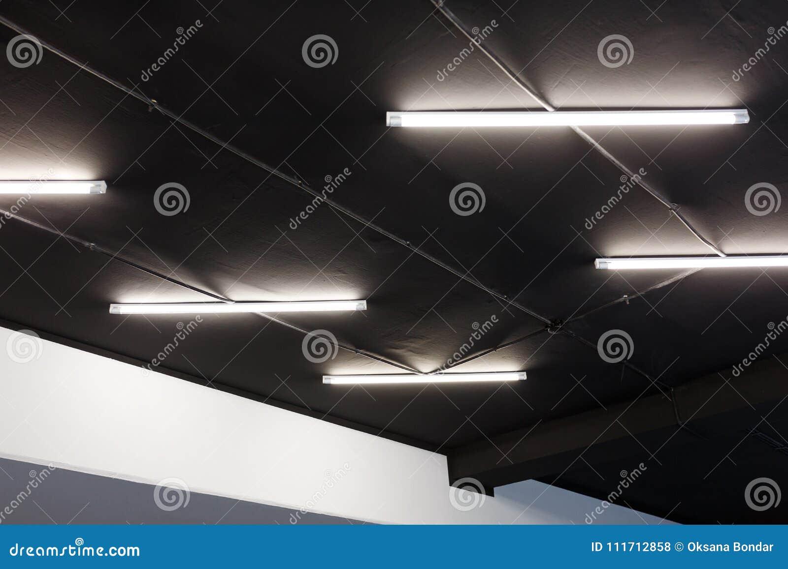 Led tube lights on black office ceiling. Minimal loft design