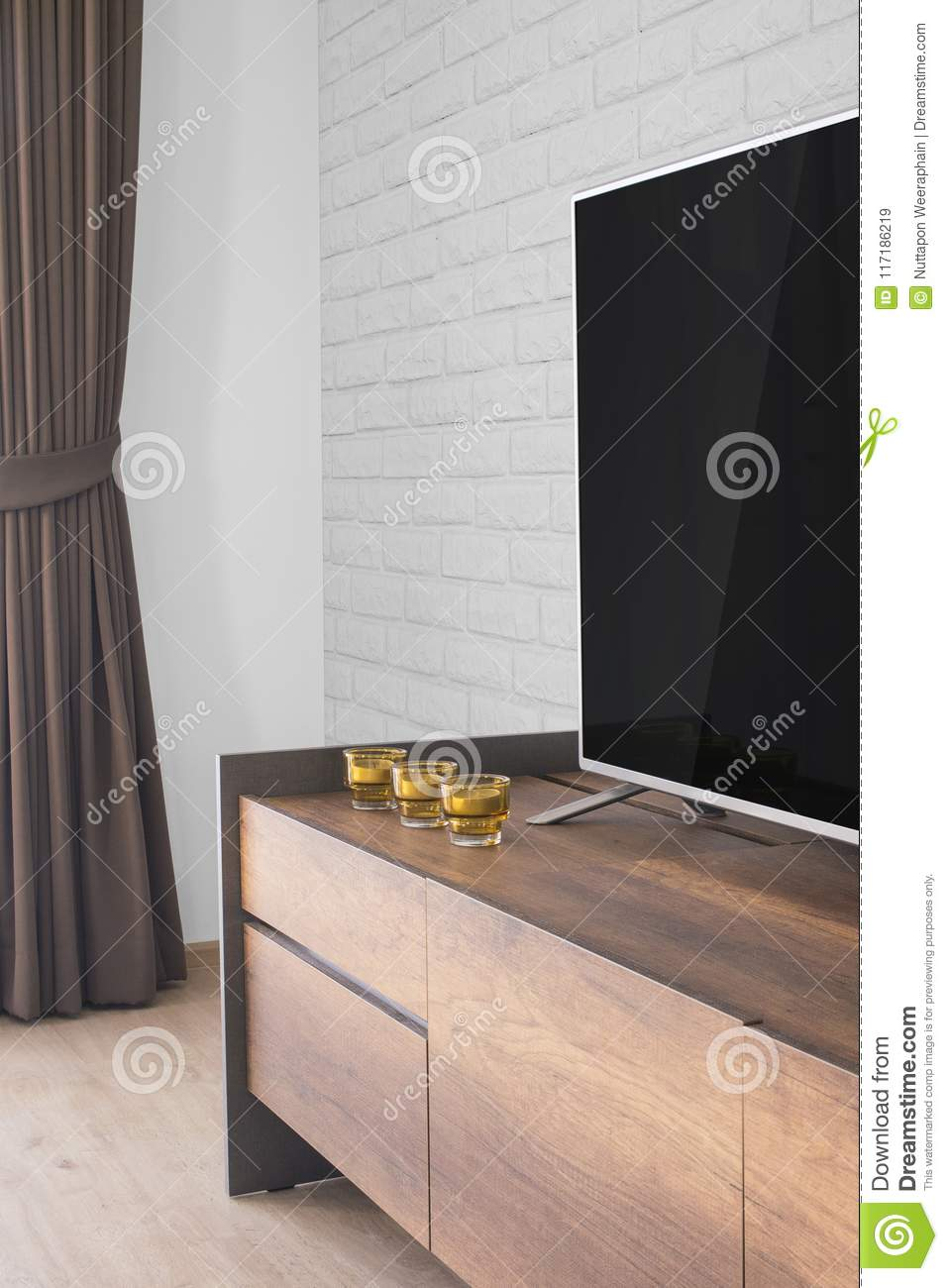 Led TV on TV stand with candles and curtain, white brick wall