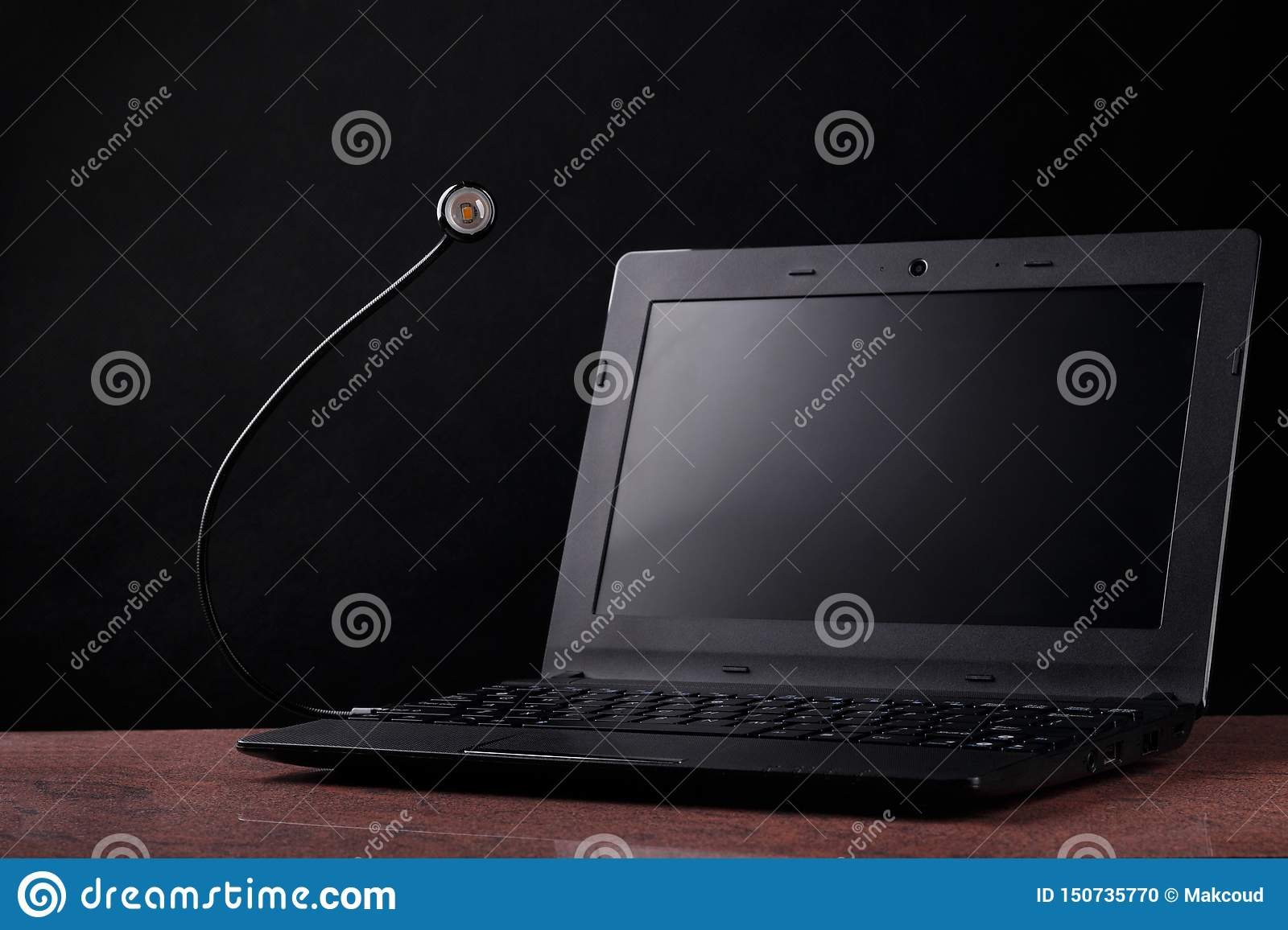 LED USB lamp connected to laptop on black background. Concept of alive usb-lamp.