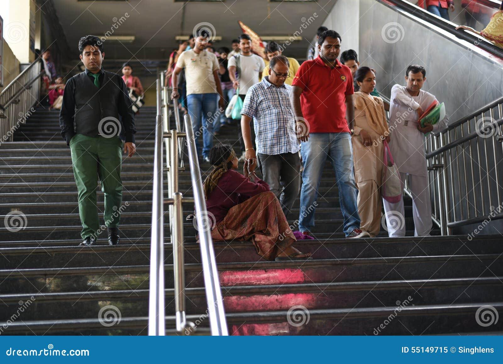 Ledare: Gurgaon Delhi, Indien: 07. Juni 2015: En oidentifierad gammal fattig kvinnatiggeri från folk på den Gurgaon tunnelbanasta