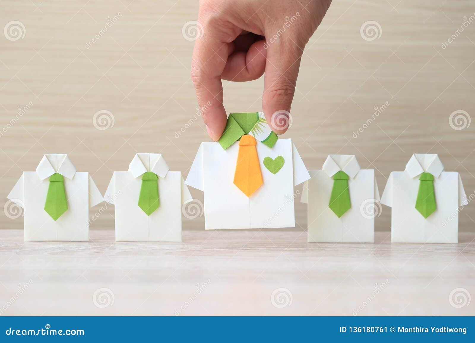 Ledarskap och teamworkbegrepp, kvinnahand som rymmer den gula skjortan för origami med bandet och leder bland den lilla gula skjo