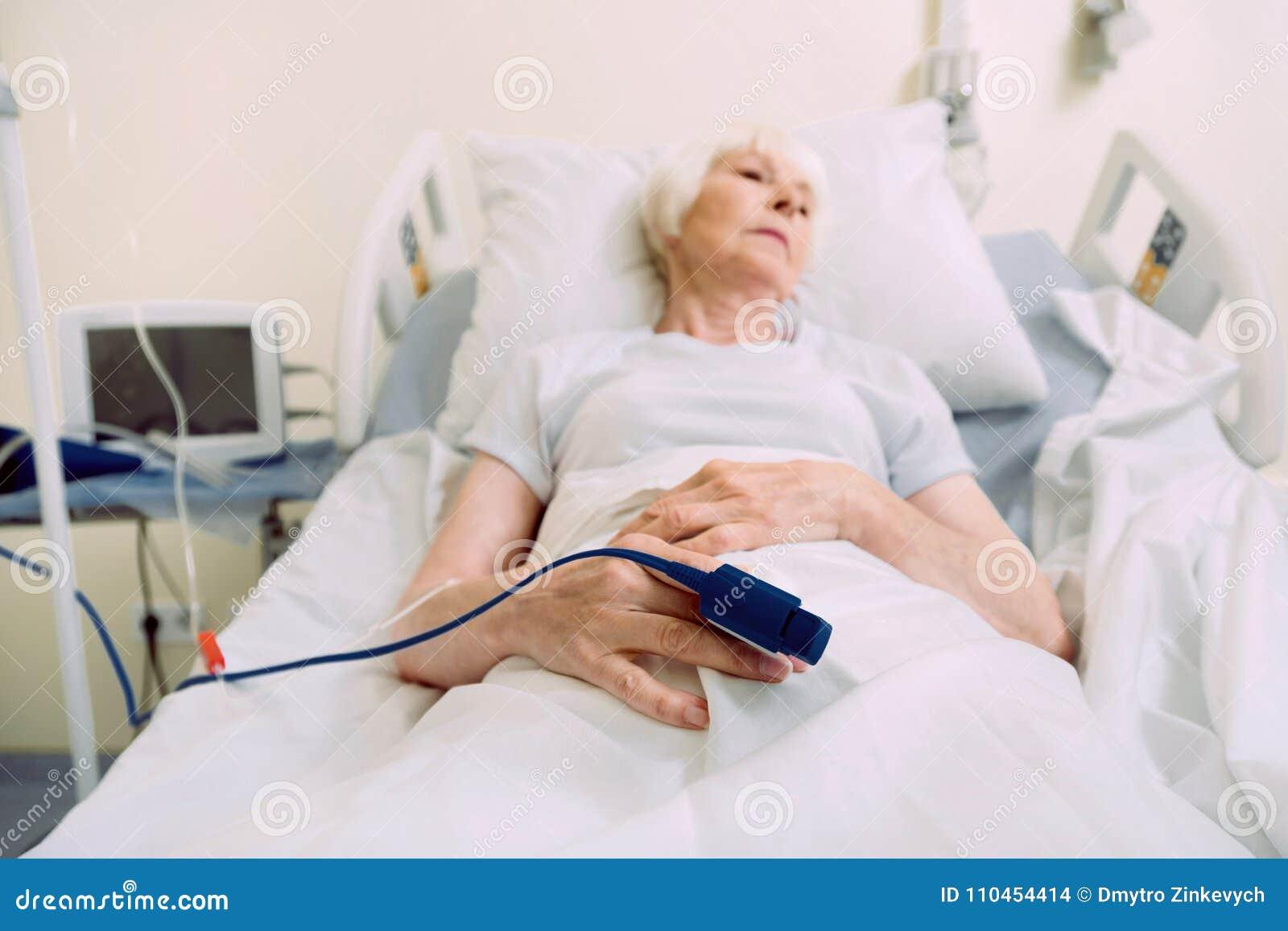 Ledsen äldre kvinna med medicinsk utrustning för hjärtahastighet på sjukhuset