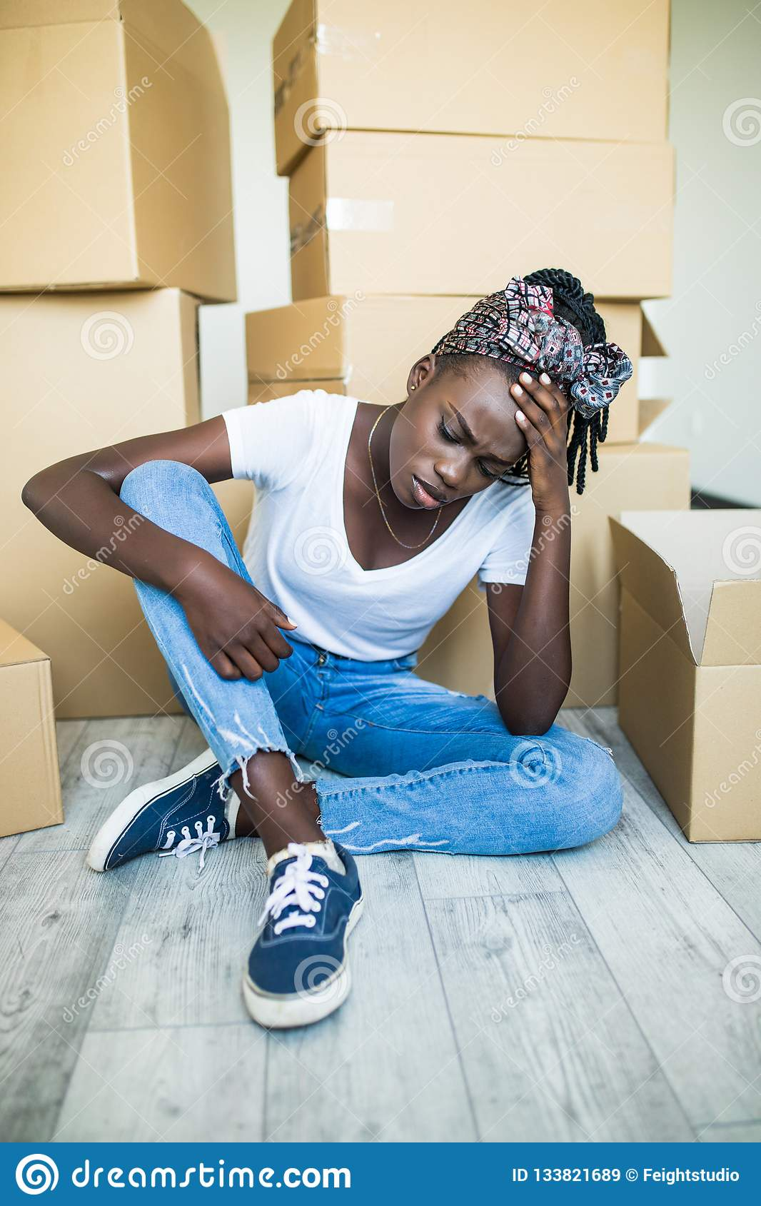 Ledsen afrikansk kvinna som unlimitedly ?r lycklig p? grund av att flytta det nya huset av hennes dr?m som sitter p? golvet med m