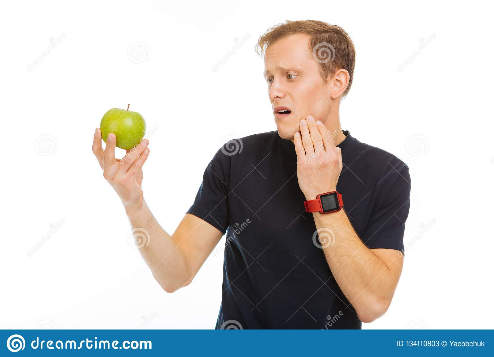 Ledsen dyster man som ser det gröna äpplet