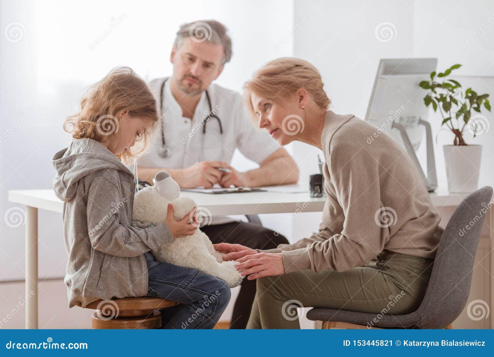 Ledsen flicka med nallebjörnen och den bekymrade farmodern på pediatricians kontor