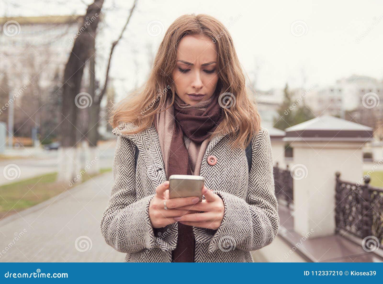 Ledsen flicka som använder telefonen på gatan