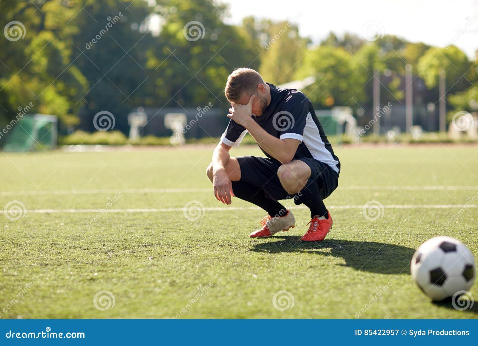 Ledsen fotbollspelare med bollen på fotbollfält