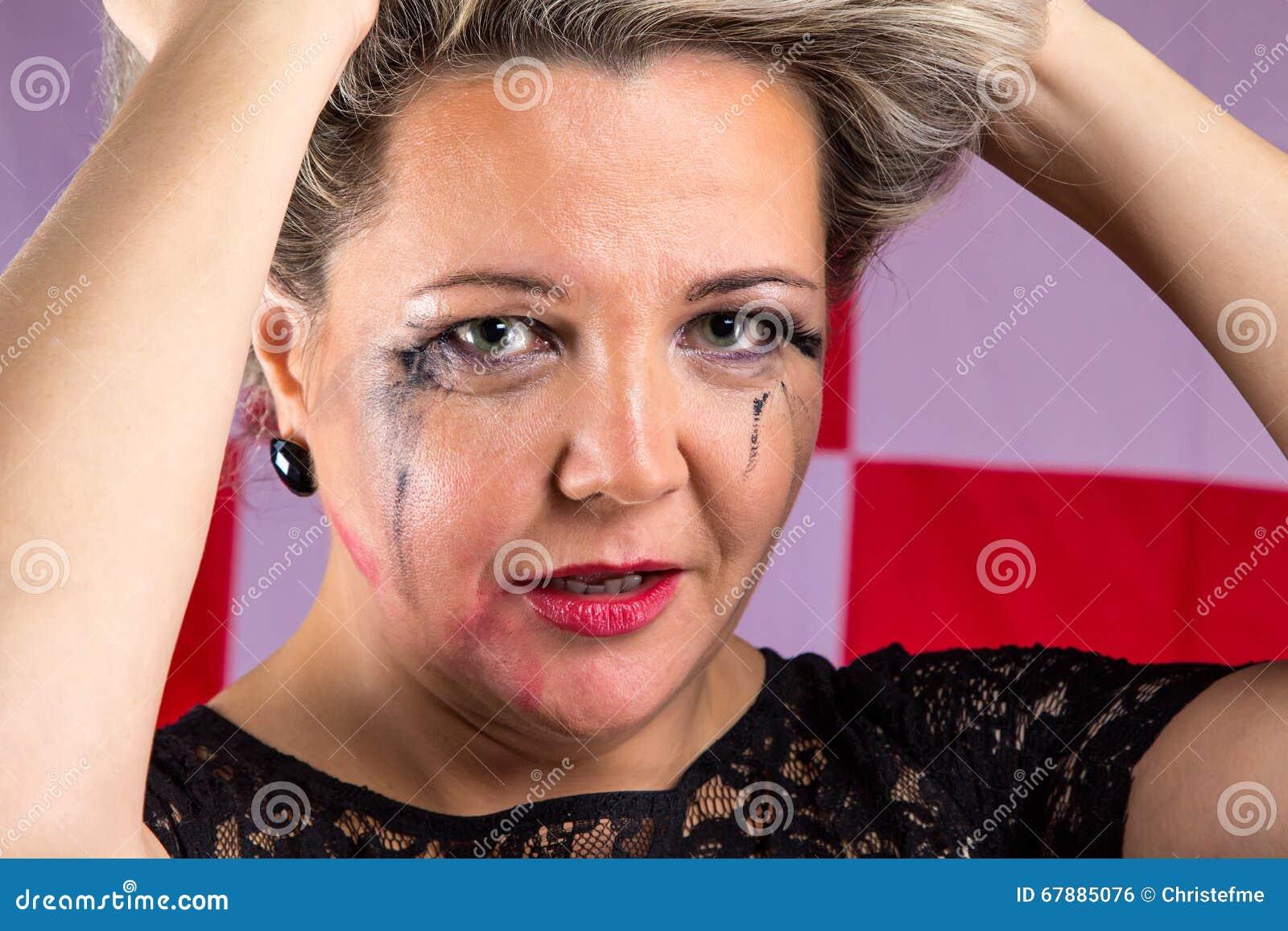 Ledsen gammal kvinna med smetat smink
