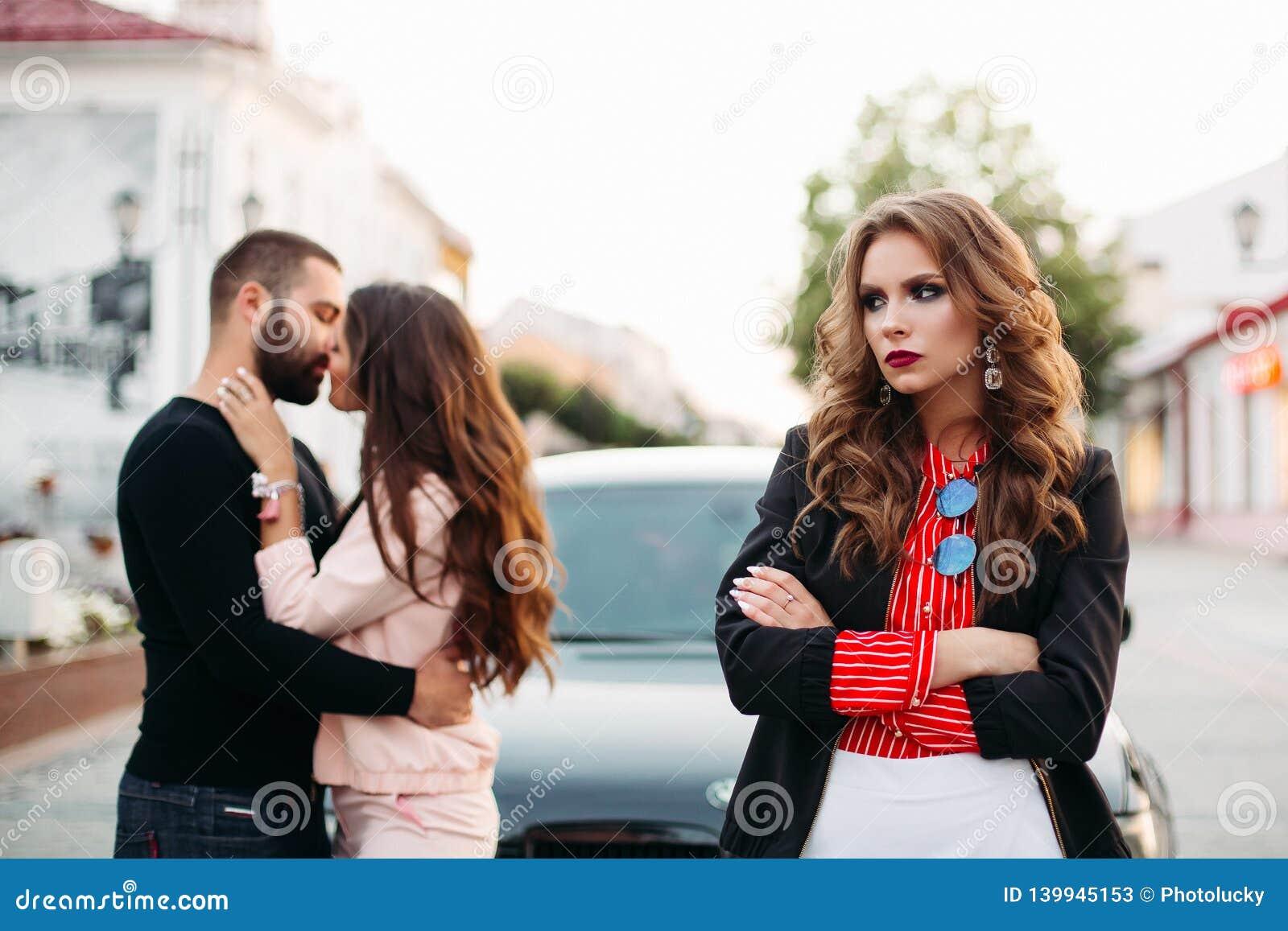Ledsen härlig kvinna med vikta armar i trendig kläder mot att kyssa par