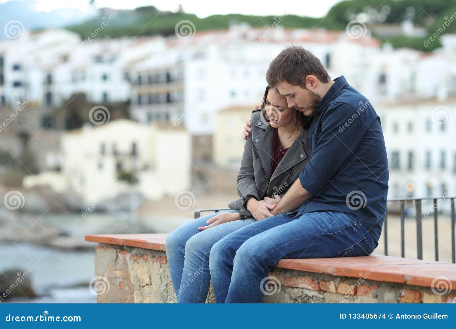 Ledsen kvinna och man som tröstar henne på en avsats