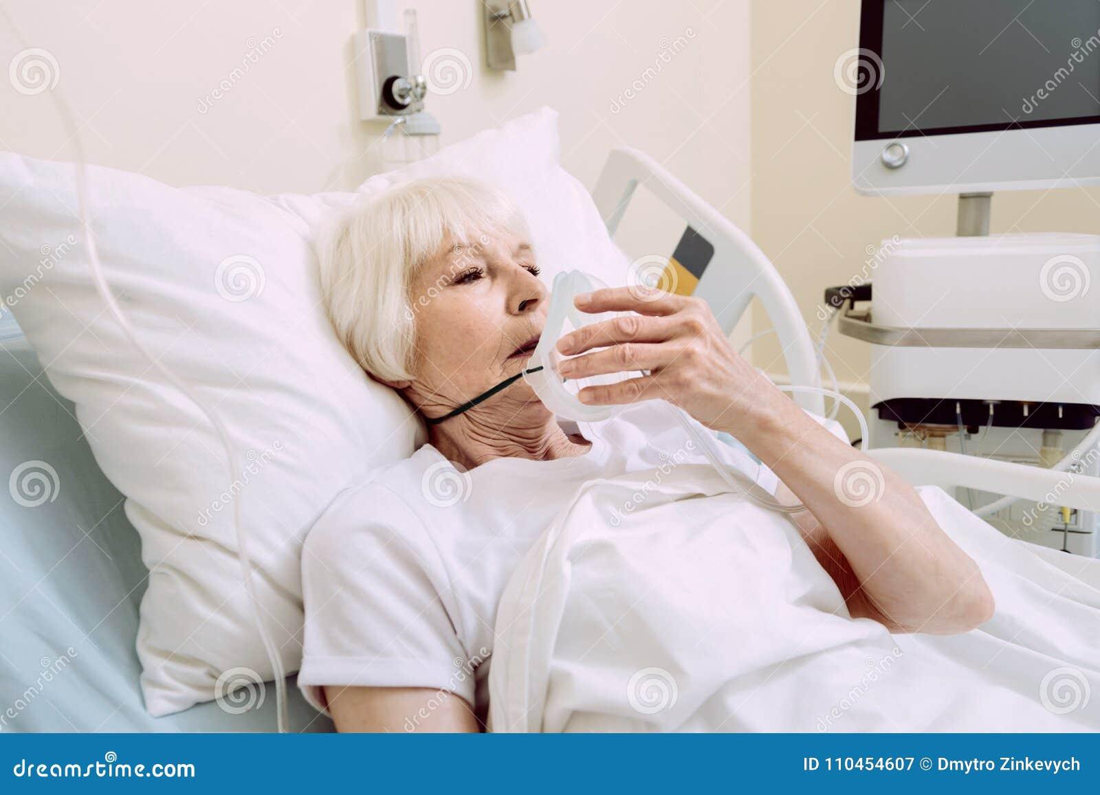 Ledsen kvinna som av tar syremaskeringen på sjukhuset