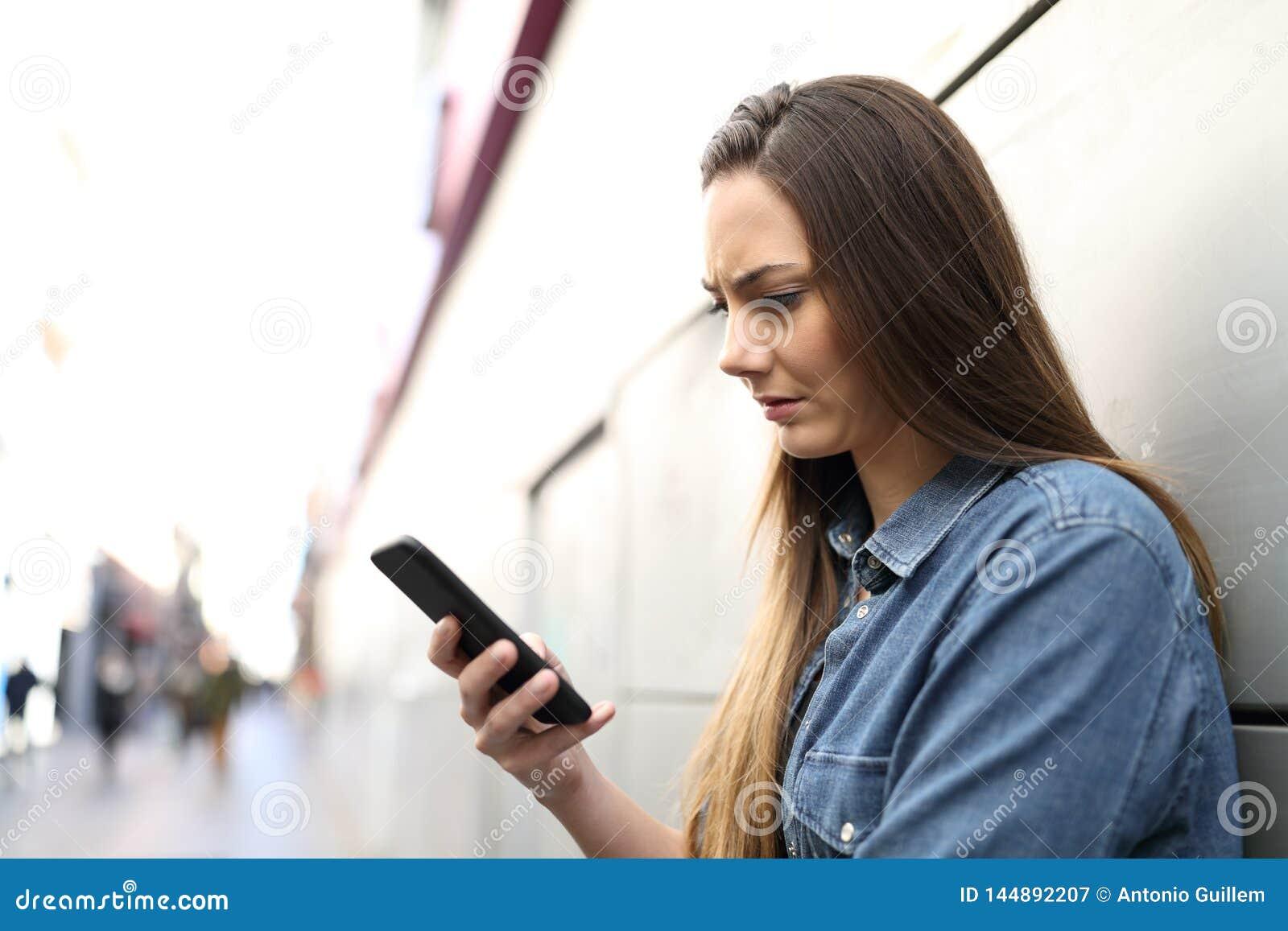 Ledsen kvinna som kontrollerar det smarta telefoninnehållet i gatan