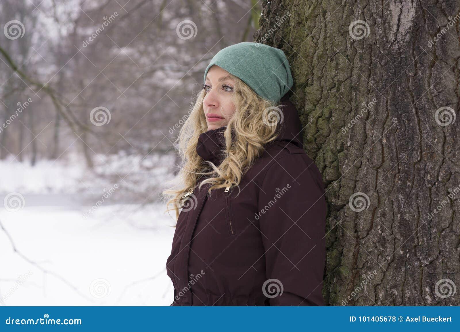Ledsen kvinnabenägenhet mot träd i vinter