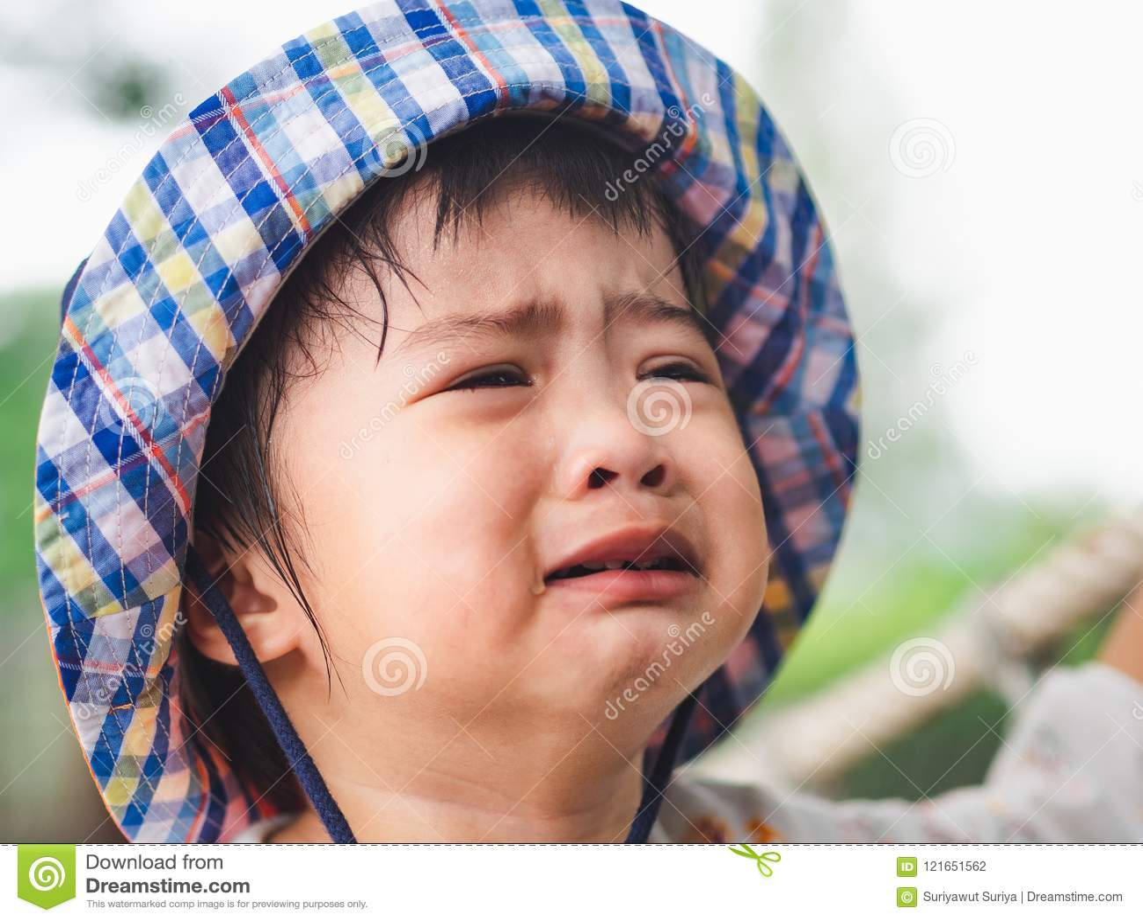 Ledsen liten flickagråtframsida på bokehbakgrund med tappningfil