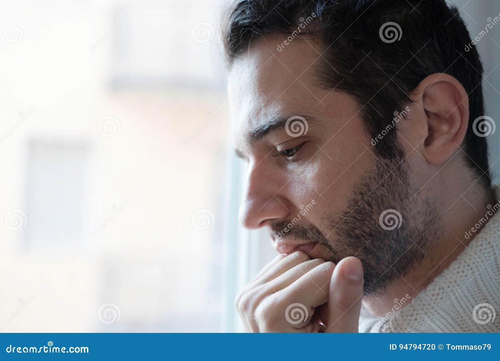 Ledsen manstående som ser ut ur fönstret