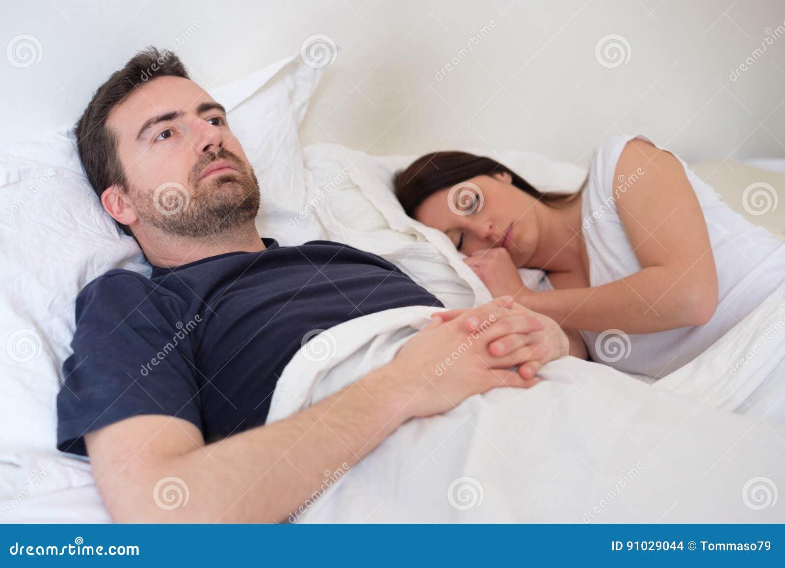 Ledsen och deprimerad man i sängen med hans fru
