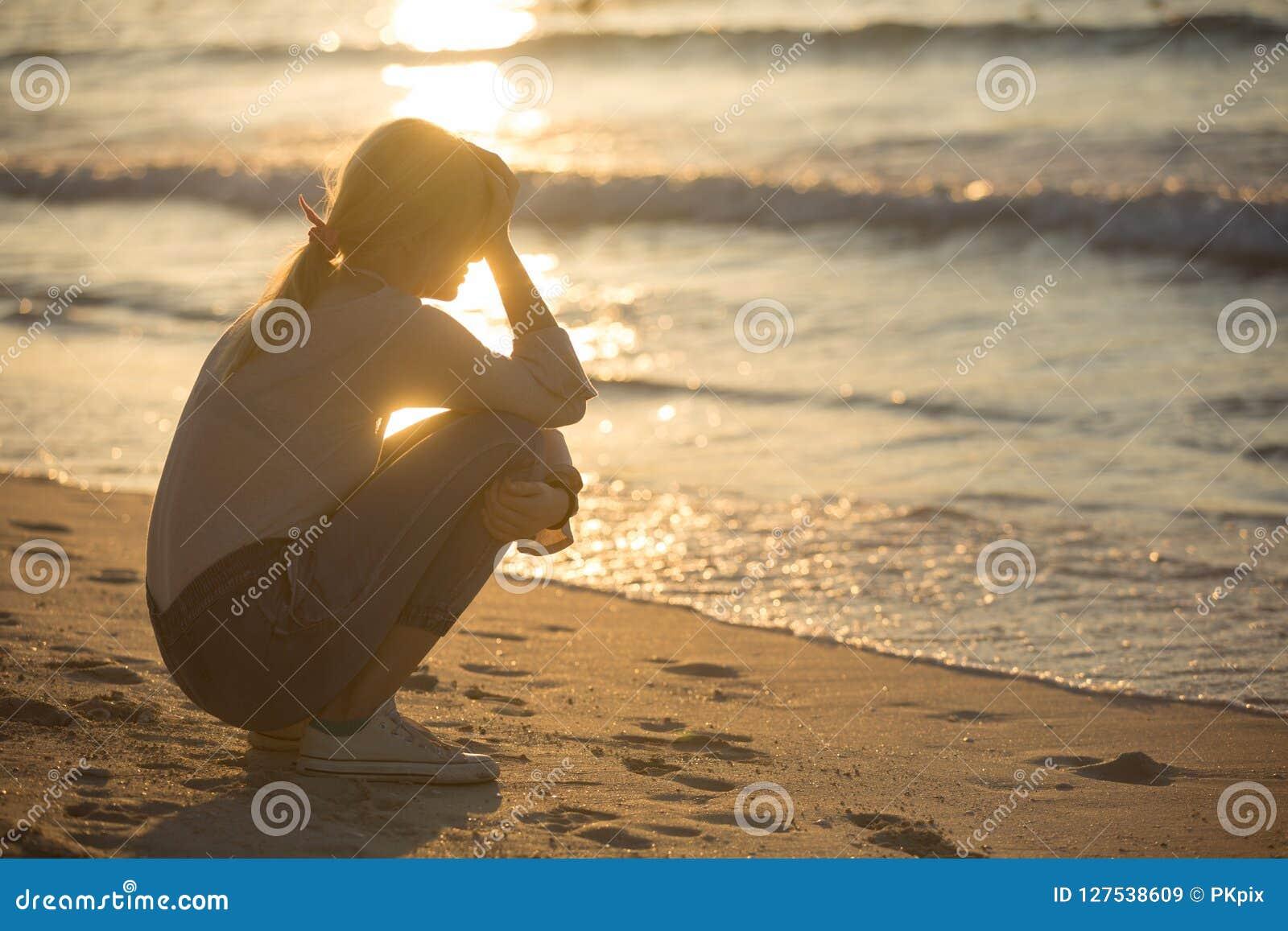 Ledsen och ensam ung kvinna på stranden