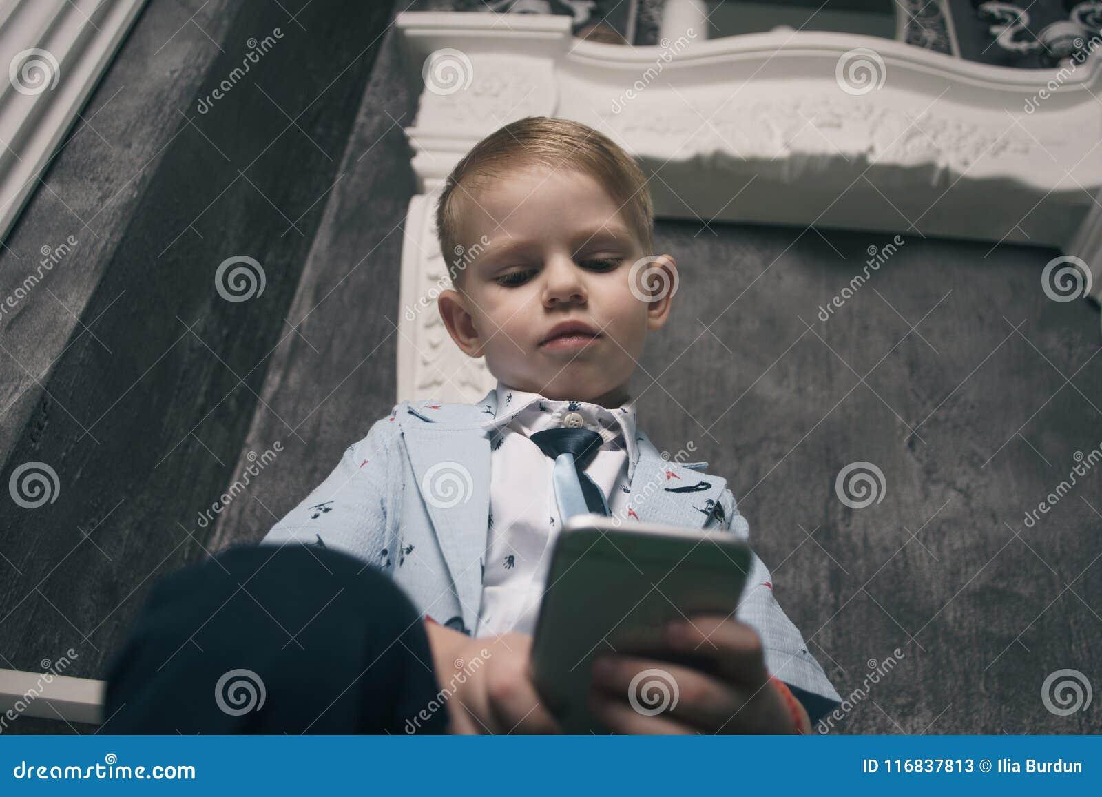Ledsen pojke som ser mobiltelefonen med