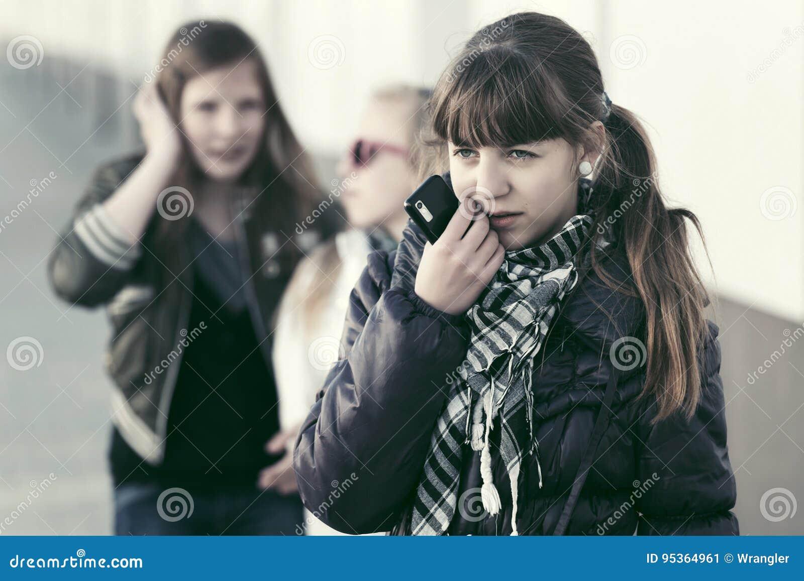 Ledsen tonårig flicka med en mobiltelefon i stadsgata