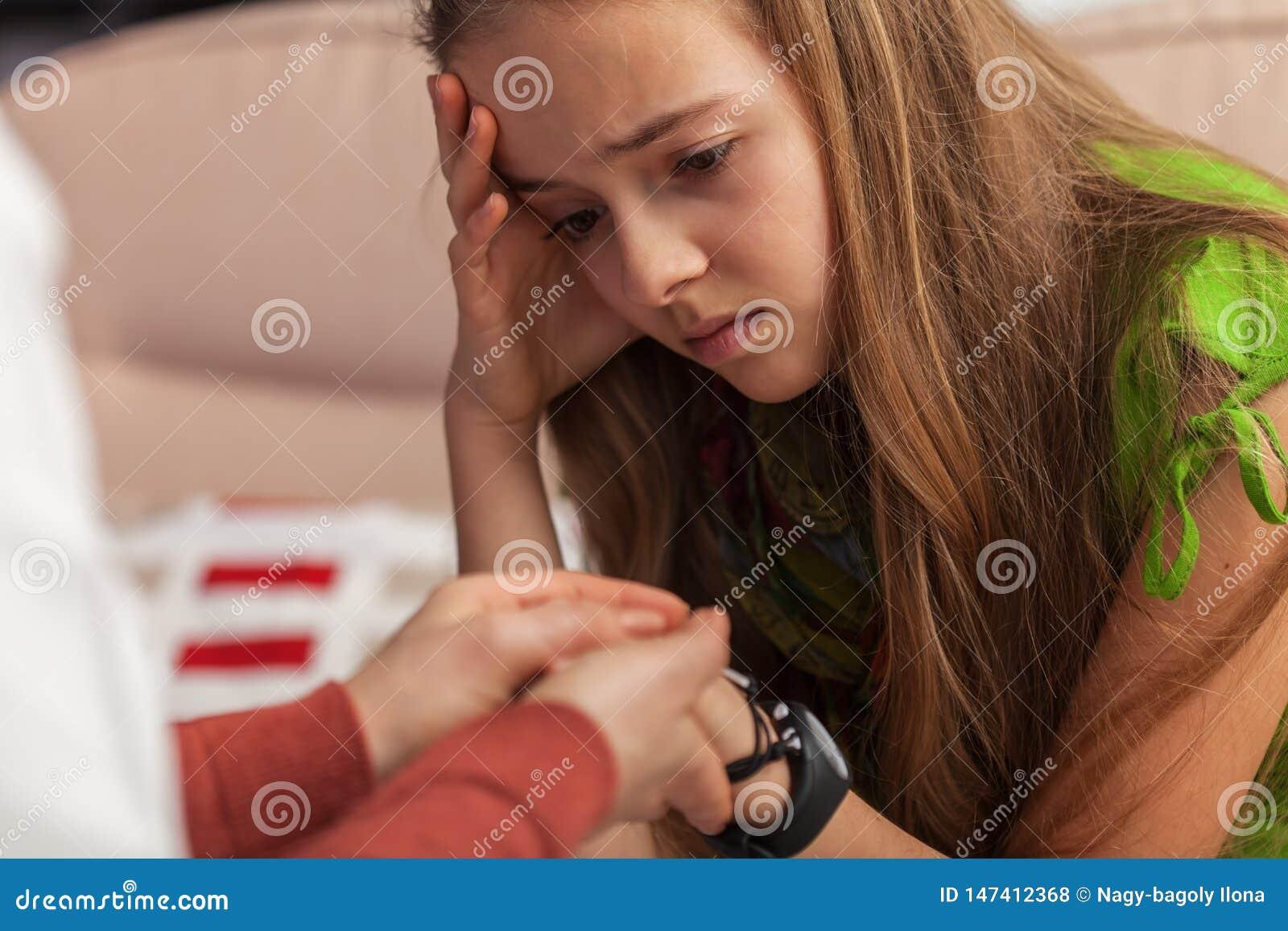 Ledsen tonåringflicka på att råda - yrkesmässigt handinnehav för kvinna och att trösta unga flickan